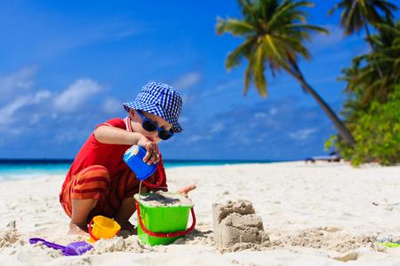 sand castle: little boy building sand castle on tropical beach