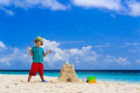 sandcastle: happy little boy with built sandcastle on tropical beach