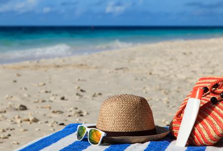 suncream: hat, bag, sun glasses and suncream on tropical beach
