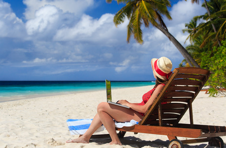 woman with laptop on tropical vacaton, modern technology
