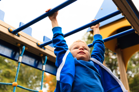 kids activities: little boy playing on monkey bars in autumn, kids sport
