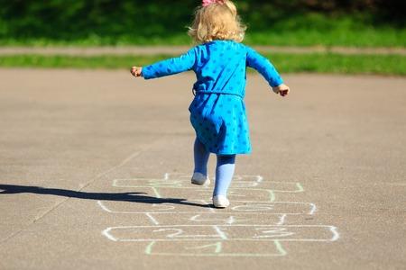 niños en recreo: niña jugando a la rayuela en el patio al aire libre