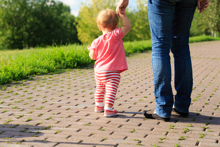 the first: little girl making first steps in the park, kids learning Stock Photo