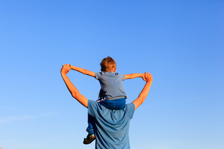 happy father and little son on shoulders play on sky Фото со стока