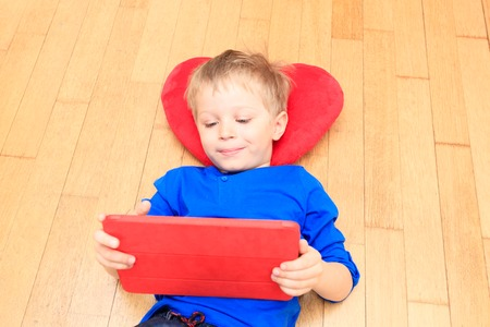 early learning: little boy looking at touch pad at home, early learning