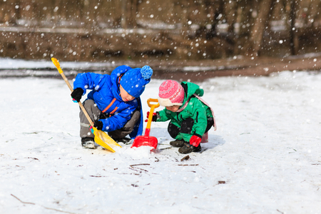 game to play: little boy and girl digging snow in winter, kids winter activities