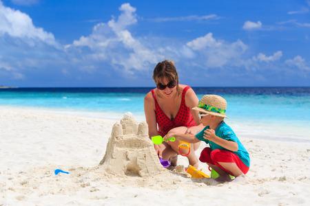 madre figlio: madre e figlio costruzione castello di sabbia sulla spiaggia di sabbia tropicale