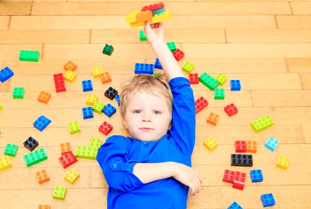 young boys: child playing with colorful plastic blocks indoor, early learning Stock Photo