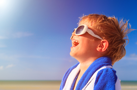 young boy smiling: happy little boy laugh wrapped in beach towel on sky, enjoy summer concept Stock Photo