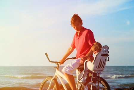 bicycle: father and baby biking at summer sea beach Stock Photo