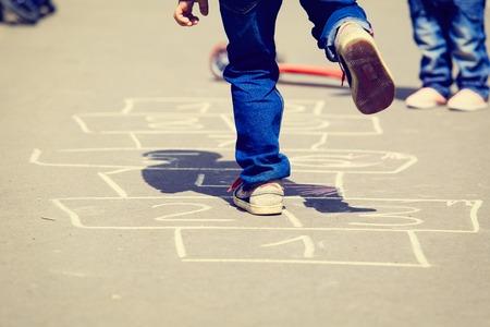 ni�os jugando: los ni�os que juegan a la rayuela en el patio al aire libre, los ni�os actividades al aire libre