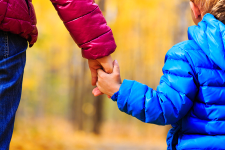 manos: mother and little son holding hands in autumn park