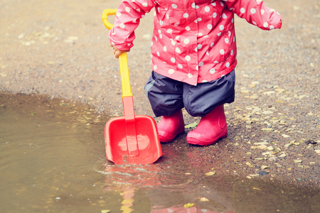 kids playing water: child playing in water puddle, kids outdoor activities Stock Photo