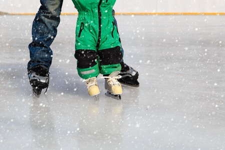 father and child learning to skate in winter snow