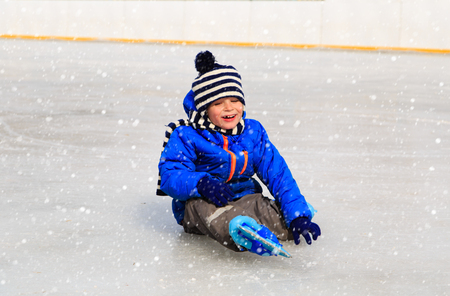 boy skating: cute little boy learning to skate in winter snow
