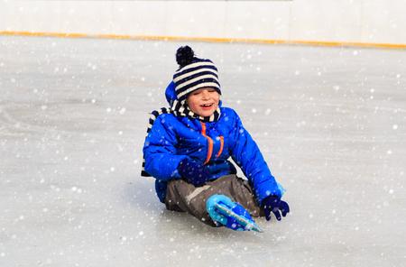 patinaje sobre hielo: niño lindo aprender a patinar en la nieve del invierno Foto de archivo