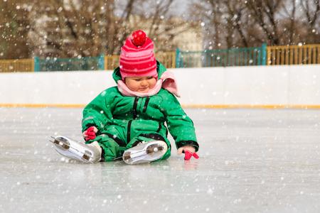 schattig klein meisje, zittend op ijs met schaatsen na de val