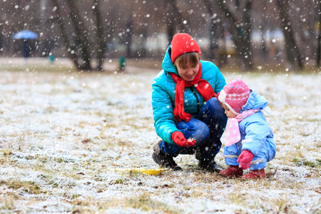 winter park: mother and little daughter playing in winter park Stock Photo