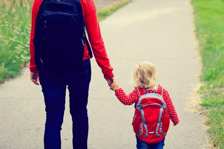 relationship mother and daughter: Mother holding hand of little daughter with backpack going to school or daycare