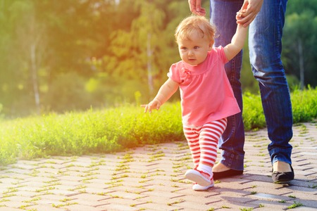 first steps of little girl with mother outdoors, kids learning