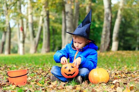 treating: little boy in halloween costume in autumn park, kids trick or treating Stock Photo