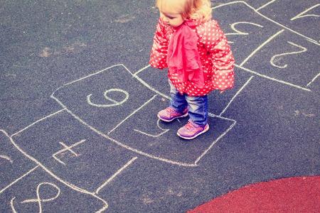 kind spelen Hinkelspel op speelplaats buitenshuis, kinderen outdoor activiteiten