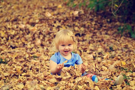 cute blonde: cute little girl playing with autumn fall leaves
