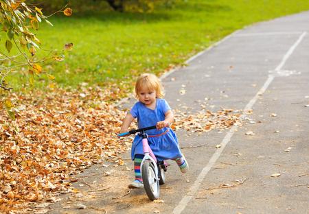 bike: cute little girl riding runbike in autumn, kids sport