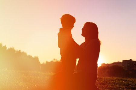 nature silhouette: happy loving mother and little son at sunset Stock Photo