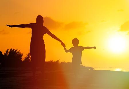 moeder en zoon met plezier op zonsondergangstrand
