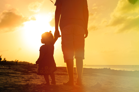 silhouettes of father and little daughter walking on beach at sunset