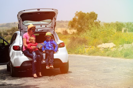 mother with kids looking at map while travel by car