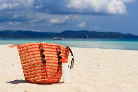 suncream: bag and suncream on tropical beach, vacation concept
