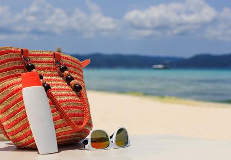 suncream: bag, sun glasses and suncream on tropical beach, vacation concept