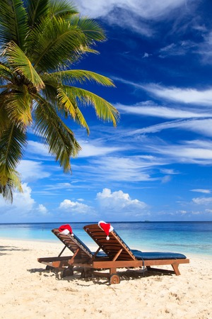 bahamas celebration: two chair lounges with red Santa hats on tropical summer beach