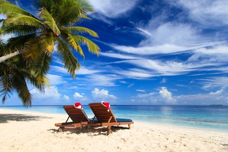 strandstoel: twee stoel lounges met rode Santa hoeden op tropische zomer strand Stockfoto