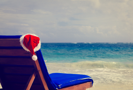 bahamas celebration: chair lounge with red Santa hat on tropical summer beach