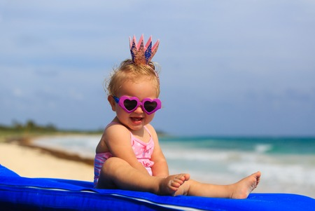 girl care: cute little baby princess on summer tropical beach