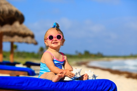 little girl swimsuit: cute little baby girl with seashells on tropical sand beach Stock Photo