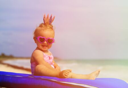 play: cute little baby princess on summer tropical beach