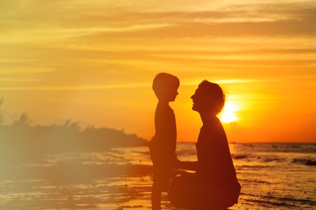 holding back: father and son holding hands at sunset sea