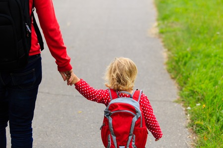 urban parenting: Mother holding hand of little daughter with backpack going to school or daycare