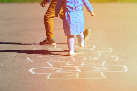 girl drawing: kids playing hopscotch on playground outdoors, children outdoor activities