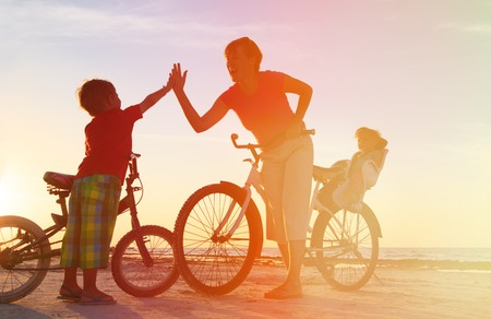 ecotourism: happy mother with kids biking at sunset beach Stock Photo