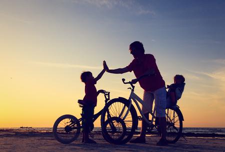 Biker familie silhouet, vader met twee kinderen op de fiets bij zonsondergang Stockfoto