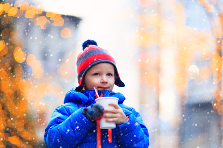 winter people: little boy having hot drink in cold winter christmas city Stock Photo