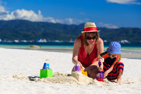 sandcastle: mother and son building sandcastle on the beach