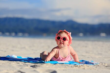 girl with towel: cute little baby girl on tropical beach Stock Photo