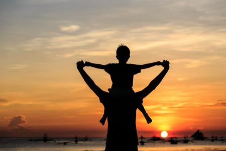 Vater und Sohn auf Himmel bei Sonnenuntergang am Strand Standard-Bild - 46082772
