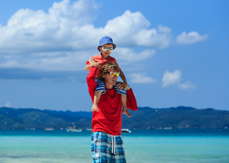 sholders: father and little son on sholders on tropical beach Stock Photo